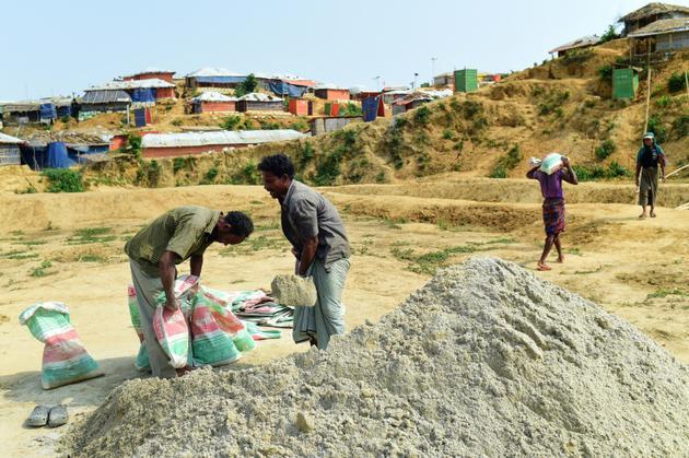 Des réfugiés rohingyas remplissent des sacs avec du sable lors de préparatifs avant l'arrivée de la mousson, le 7 mai 2018 au camp de Kutupalong, au Bangladesh [Munir UZ ZAMAN / AFP]