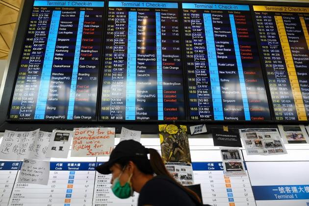 Panneaux d'affichage indiquant l'annulation des vols en partance et à destination de l'aéroport international de Hong Kong le 12 août 2019 [Manan VATSYAYANA / AFP]