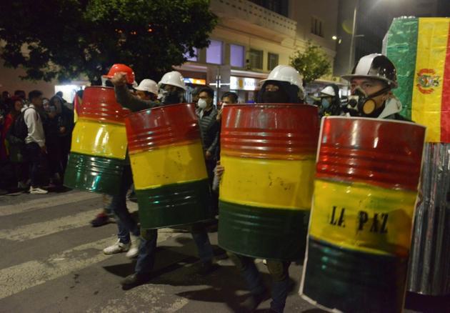 Des manifstants d'opposition se protègent avec des boucliers improvisés à La Paz le 8 novembre 2019 [AIZAR RALDES / AFP]