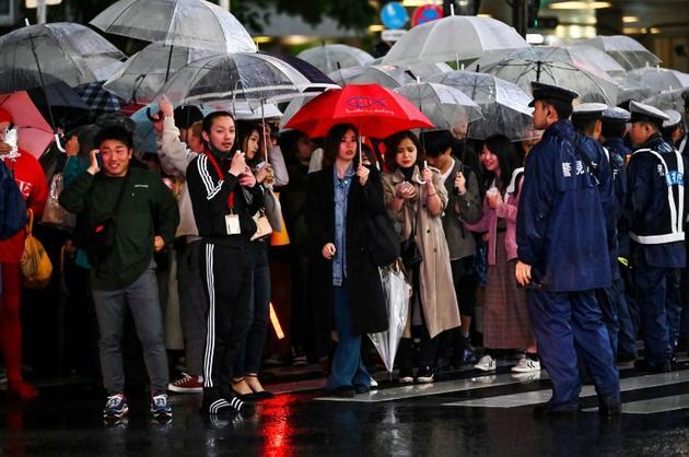 La nouvelle ère impériale Reiwa commmence sous la pluie pour des Japonais massés dans le quartier de Shibuya à Tokyo au moment de la cérémonie d'abdication, le 30 avril 2019. [CHARLY TRIBALLEAU / AFP]