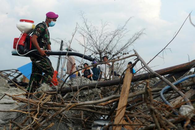 Un soldat indonésien pulvérise du désinfectant à Petobo, près de Palu en Indonésie, le 16 octobre 2018, près d'un mois après le passage d'un tsunami dévastateur [OLAGONDRONK / AFP/Archives]