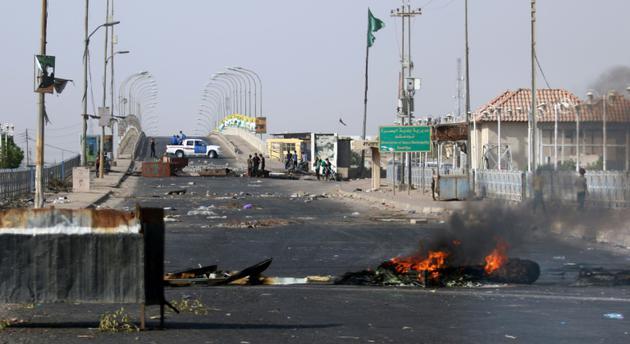 Des manifestants bloquent le passage et brûlent des pneus dans la ville de Bassora en Irak, le 12 juillet 2018 [Haidar MOHAMMED ALI / AFP]