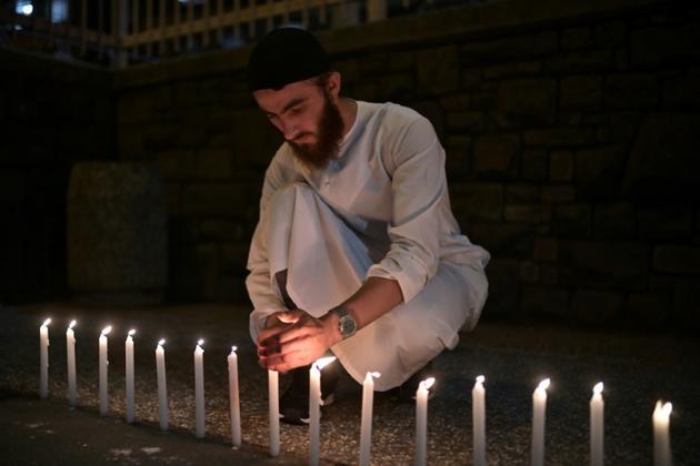 Un homme allume des bougies pour rendre hommage aux 49 victimes de l'attaque de deux mosquées à Christchurch, le 16 mars 2019 [Anthony WALLACE / AFP]