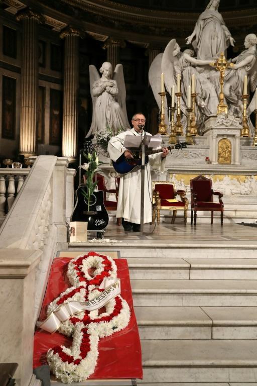 Un prêtre joue de la guitare pendant la messe hommage à Johnny Hallyday à l'égilse de la Madeleine à Paris, le 9 décembre 2018 [JACQUES DEMARTHON / AFP]