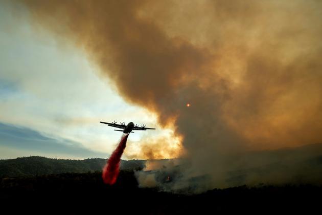 Un avion bombardier d'eau largue un produit ignifugeant pour freiner le Ranch Fire, incendie faisant partie du Mendocino Complex,  près de la localité de Clealarke Oaks, le 5 août 2018 [NOAH BERGER / AFP]