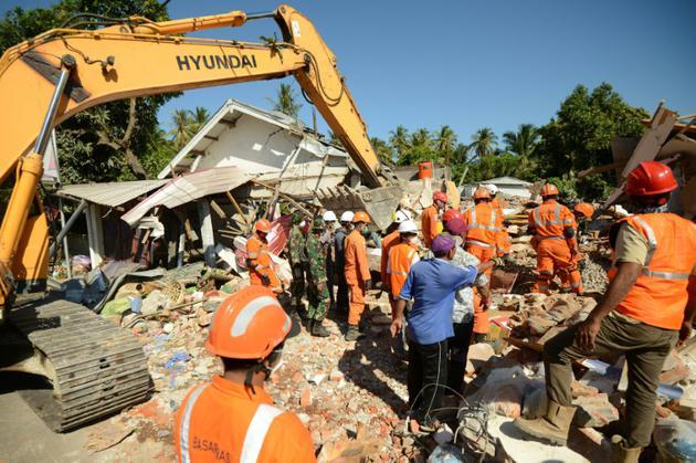 Recherches dans les décombres de bâtiments effondrés, le 8 août 2018 à Sigar Penjalin, en Indonésie, après le sésime meurtrier de dimanche sur l'île de Lombok [SONNY TUMBELAKA / AFP]