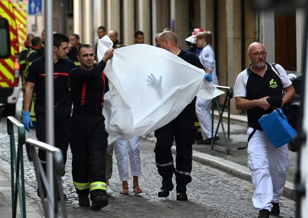 Des pompiers transportent un blessé après l'explosion d'un colis piégé dans une rue de Lyon, le 24 mai 2019 [PHILIPPE DESMAZES / AFP]