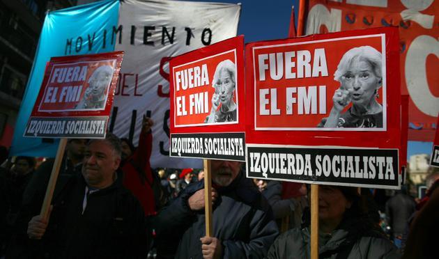 """Des manifestants brandissent des pancartes """"FMI dehors"""" lors du G20 à Buenos Aires le 21 juillet 2018 [AGUSTIN MARCARIAN / AFP]"""