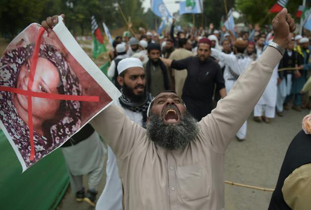 Un partisan du parti musulman extrémiste ASWJ (Ahle Sunnat Wal Jamaat) proteste contre l'acquittement de la chrétienne Asia Bibi dont il brandit le portrait barré de rouge, le 2 novembre 2018 à Islamabad [AAMIR QURESHI / AFP]