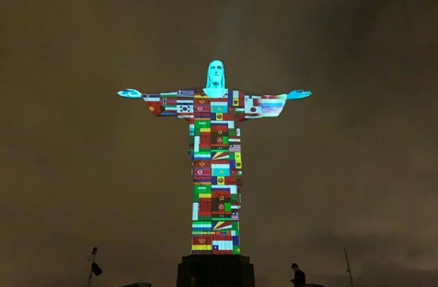 Projection des drapeaux de tous les pays infectés par le coronavirus, sur le Christ rédempteur de Rio de Janeiro, le 18 mars 2020   [FLORIAN PLANCHEUR / AFP]