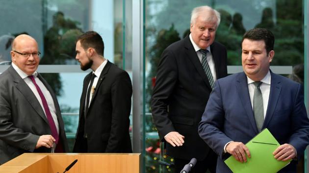 Les ministres allemands de l'Economie Peter Altmaier (G), du Travail Hubertus Heil (D) et de l'Intérieur Horst Seehofer (2eD) arrivent à une conférence de presse sur un projet de loi sur l'immigration, à Berlin le 19 décembre 2018 [John MACDOUGALL / AFP]