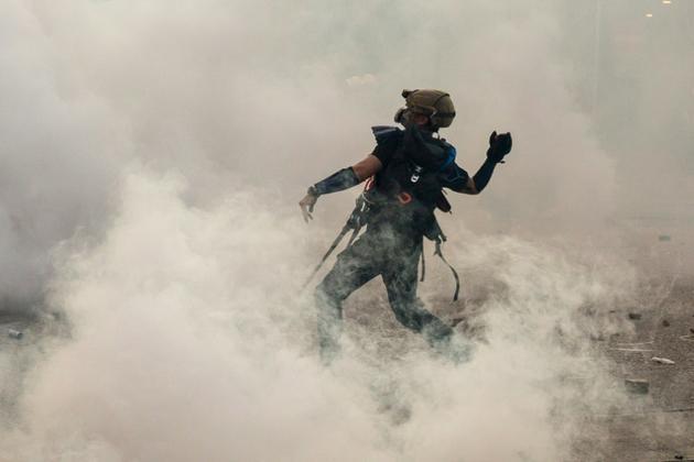 Un manifestant prodémocratie lance une brique sur les forces de l'ordre qui viennent de tirer des gaz lacrymogènes, le 5 août 2019 à Hong Kong [Isaac Lawrence / AFP/Archives]