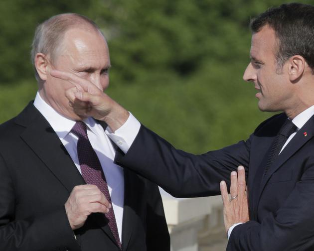 Le président russe Vladimir Poutine avec son homologue français Emmanuel Macron le 24 mai 2018 à Saint-Pétersbourg [Dmitry LOVETSKY / POOL/AFP]