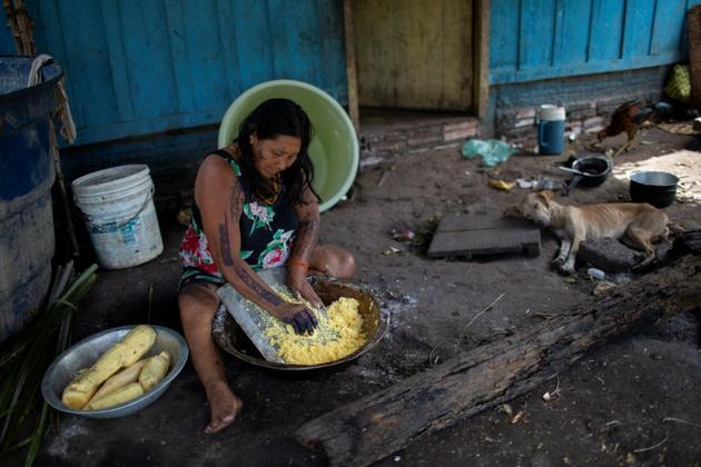 Une Arara prépare le repas au camp de la tribu Laranjal en Amazonie brésilienne, le 15 mars 2019 [Mauro Pimentel / AFP]