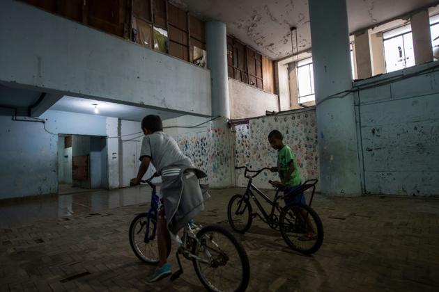 Des enfants font du vélo dans un immeuble squatté de la banlieue de Sao Paulo au Brésil, le 14 mai 2018 [NELSON ALMEIDA / AFP/Archives]