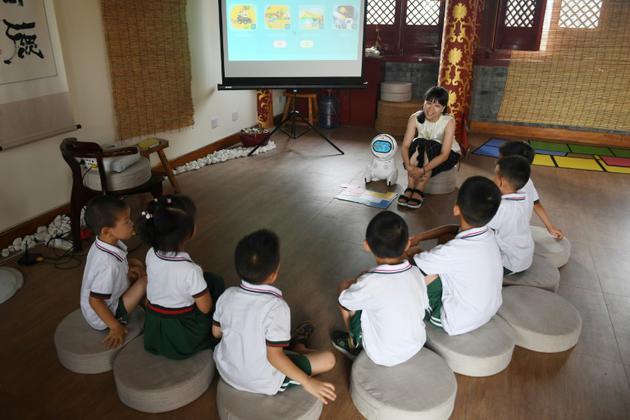 L'éducatrice Candy Xiong présente le robot Keeko dans une maternelle chinoise, le 30 juillet 2018 [GREG BAKER / AFP]