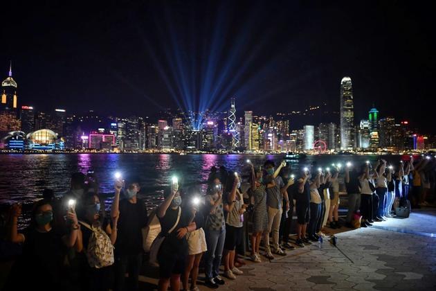 Des manifestants pro-démocratie forment une chaîne humaine,  le long de Victoria Harbour, le 23 août 23019 à Hong Kong [Lillian SUWANRUMPHA / AFP]