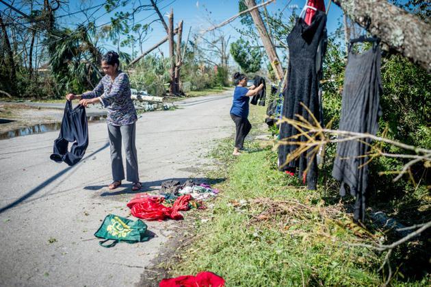 Une famille accroche des vêtements à des arbres afin de les faire sêcher, après le passage de l'ouragan Michael, le 11 octobre 2018 à Panama City (Floride).  [Emily KASK / AFP]