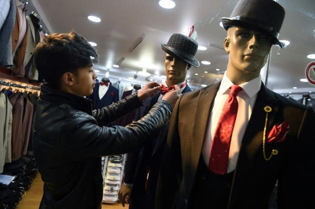 Le vendeur afghan Ali Haidiri habille un mannequin dans une boutique de vêtements pour hommes, le 18 février 2019 à Kaboul [WAKIL KOHSAR / AFP]