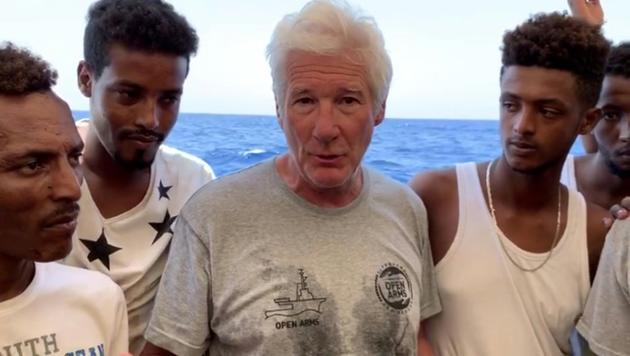 Extrait d'une vidéo de l'ONG espagnole Proactiva Open Arms, montrant l'acteur américain Richard Gere et des migrants à bord d'un navire affrêté par l'association, le 9 août 2019, dans la mer Méditerranée. [HO / PROACTIVA OPEN ARMS/AFP]
