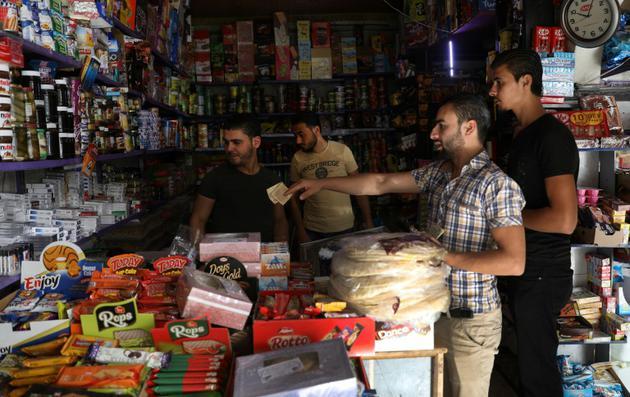 Des Syriens font leurs emplettes dans un magasin de la ville de Binnish contrôlée par les rebelles dans la province d'Idleb dans le nord-ouest de la Syrie, le 15 octobre 2018 [OMAR HAJ KADOUR / AFP]