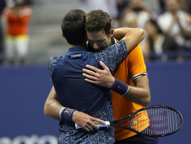 Novak Djokovic (g), vainqueur de l'US Open, dans les bras de son adversaire Juan Martin del Potro (d), dimanche 9 septembre 2018 à New York. [Eduardo MUNOZ ALVAREZ / AFP]