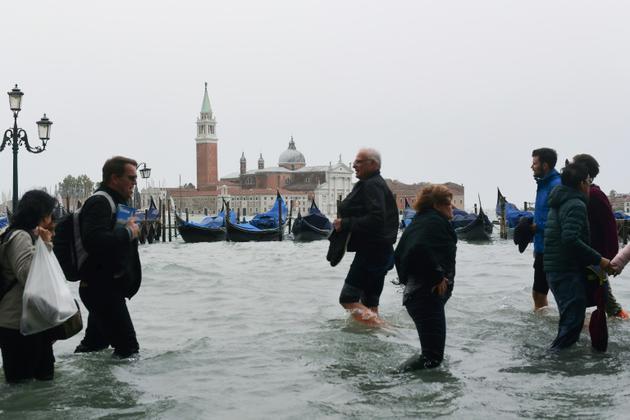 Des gens marchent malgré les inondations à Venise le 29 octobre 2018<br />  [Miguel MEDINA / AFP]