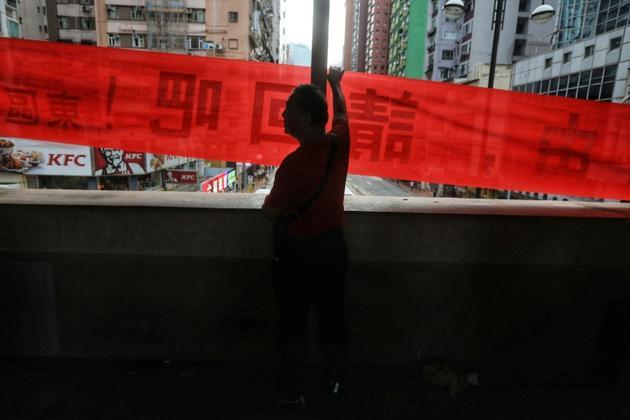 Un manifestant brandit une banderole pro-démocratie le 11 août 2019 à Hong Kong [Vivek Prakash / AFP]