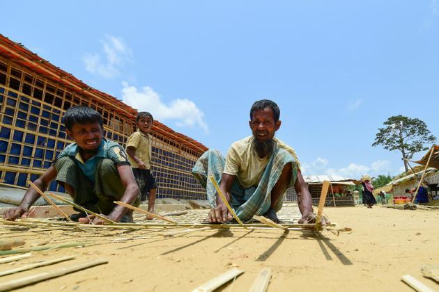 Des réfugiés rohingyas préparent des barrières en bambous avant l'arrivée de la mousson, le 9 mai 2018 dans le camp de Kutupalong, au Bangladesh [Munir UZ ZAMAN / AFP]