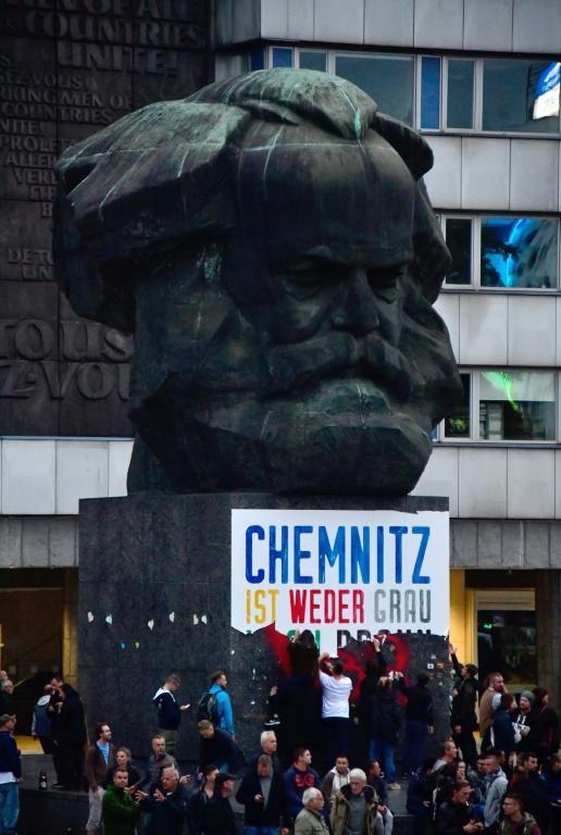 """Chemnitz n'est ni grise ni brune"""", pouvait-on lire sur une immense affiche collée sous l'imposant buste de Karl Marx situé devant l'Hôtel de Ville. Chemnitz fut baptisée Karl-Marx-Stadt durant la période communiste en RDA. [John MACDOUGALL / AFP]"""