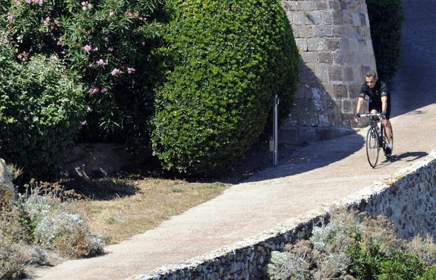 L'ancien président français Nicolas Sarkozy sort à vélo du fort de Brégançon où il passe ses vacances le 23 juillet 2011 [ANNE-CHRISTINE POUJOULAT / AFP/Archives]
