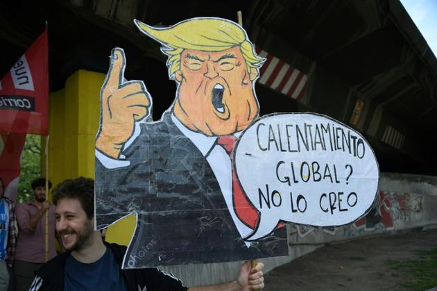 """Un homme porte une caricature de Donald Trump disant """"Réchauffement global? Je n'y crois pas"""", le 30 novembre 2018 à Buenos Aires. Le climatoscepticisme du président américain est un modèle pour les certaines Européens [MARTIN BERNETTI / AFP/Archives]"""