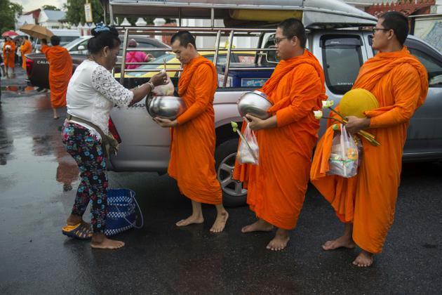 Des moines reçoivent des offrandes, le 23 octobre 2018 près d'un temple bouddhiste à Bangkok [Romeo GACAD / AFP]