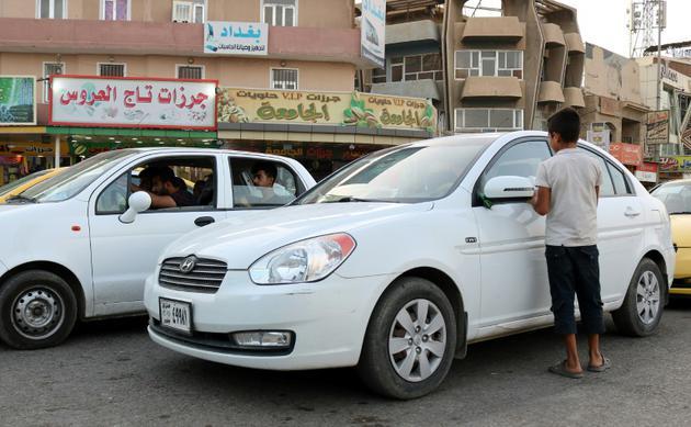 Un enfant irakien s'approche d'une voiture dans une rue de Mossoul, où des enfants orphelins errent pour mendier ou vendre des objets futiles pour survivre, un an après la reprise par l'armée irakienne de la ville aux jihadistes, le 7 juillet 2018  [Waleed AL-KHALID / AFP Photo]