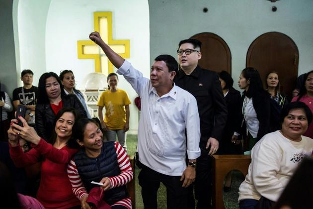 Le sosie du président philippin Rodrigo Duterte, connu sous le nom de Cresencio Extreme, en compagnie du sosie de Kim Jong Un, à un service religieux à Hong Kong le 3 février 2019. [ISAAC LAWRENCE / AFP]