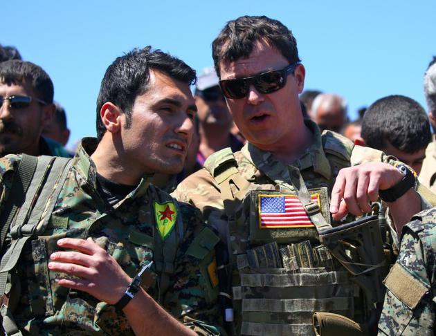 Un officier américain (à droite) parle à un combattant de la milice kurde YPG sur un site de bombardements turcs dans le nord-est de la Syrie, le 25 avril 2017 [DELIL SOULEIMAN / AFP/Archives]