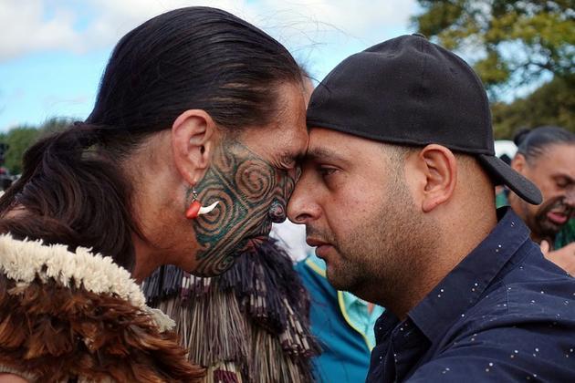 """Un musulman (à droite) et un non-musulman pratiquent le """"hongri"""", salutation traditionnelle maori, pendant la prière du vendredi devant la mosquée al-Nour de Christchurch, le 22 mars 2019 [Jerome TAYLOR / AFP]"""