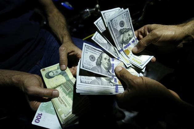 Un homme échange des rials iraniens contre des dollars américains à Téhéran, le 8 août 2018  [ATTA KENARE / AFP]