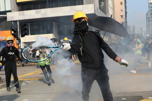 Un manifestant renvoie avec une raquette de tennis une grenade lacrymogène tirée par la police, dans le quartier de Tsim Sha Tsui, le 20 octobre 2019 à Hong Kong [Dale DE LA REY / AFP/Archives]