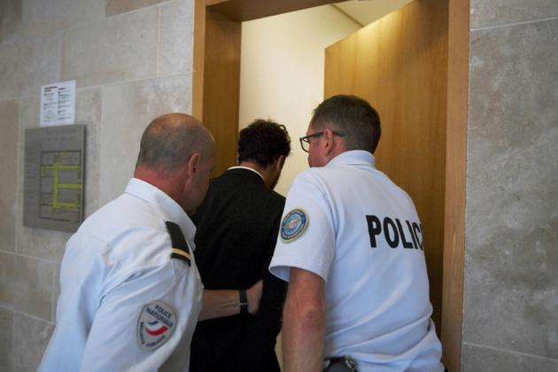 Le chanteur marocain Saad Lamjarred (C) escorté par deux policiers dans un tribunal d'Aix-en-Provence, le 18 septembre 2018 [Boris HORVAT                         / AFP]