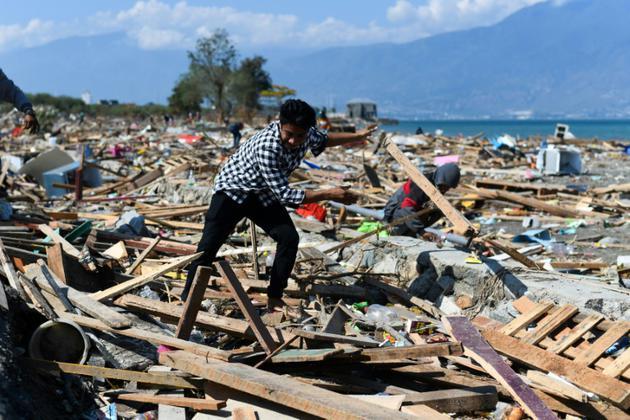 Un survivant du séisme meurtrier qui a frappé Palu sur l'île des Célèbes en Indonésie tente de récupérer des objets dans les décombres, le 1er octobre 2018 [Jewel SAMAD / AFP]