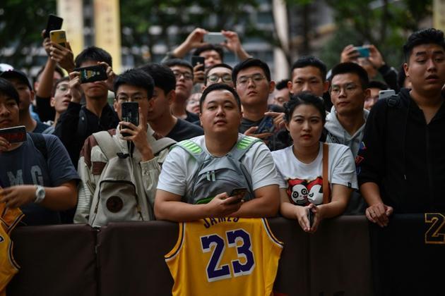 Des fans attendent à l'extérieur de l'hôtel les joueurs de la NBA qui doivent disputer un match de présaison entre les Nets et les Lakers, à Shanghai, le 9 octobre 2019 [HECTOR RETAMAL / AFP]