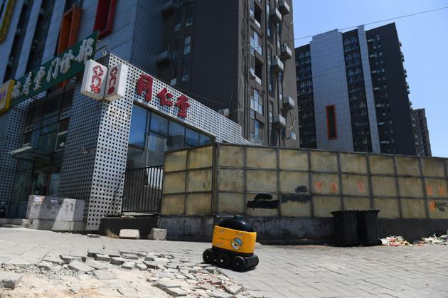 Un robot Zhen se dirige vers un ensemble d'immeubles résidentiels pour assurer une livraison lors d'une démonsration à Pékin, le 28 juin 2018 [GREG BAKER / AFP]