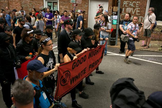 Des membres Antifa dans une rue de Charlottesville, le 11 août 2018 en Virginie, un après après la mort de Heather Heyer, manifestante antiraciste tuée dans des heurts avec des suprématistes blancs [Logan Cyrus / AFP]
