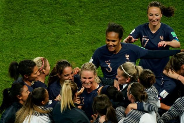 La milieu Amandine Henry (c) félicitée par ses coéquipières après son but face à la Corée du Sud, en match d'ouverture du Mondial au Parc des Princes, le 7 juin 2019 [Kenzo TRIBOUILLARD / AFP]