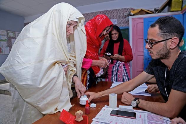 Une femme trempe son doigt dans un pot d'encre après avoir voté, dans un bureau de vote de Tunis, le 15 septembre 2019. [FETHI BELAID / AFP]