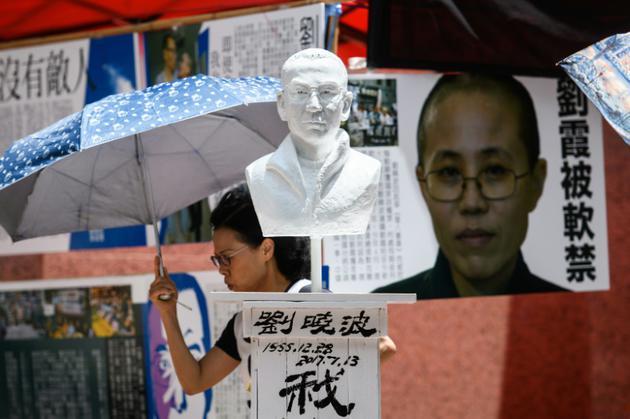 Un buste du prix Nobel Liu Xiaobo (C), décédé en juillet 2017, et un portrait de son épouse Liu Xia (D) lors d'une commémoration le 1er juin 2018 à Hong Kong avant le 29ème anniversaire de la répression en 1989 sur la place Tiananmen à Pékin [Anthony WALLACE / AFP/Archives]