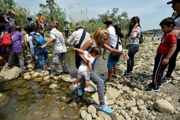 Des personnes franchissent illégalement la frontière entre la Colombie et le Venezuela au moyen de gués sur la rivière Tachira, le 28 février 2019 [Luis ROBAYO / AFP]