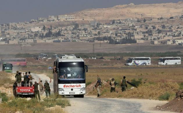Des bus transportant des civils et des insurgés évacués des localités de Foua et Kefraya, le 19 juillet 2018 en Syrie [George OURFALIAN / AFP]