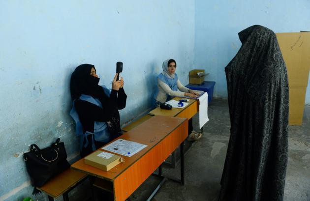 Une employée de la Commission électorale scanne le visage d'une votante lors des législatives, le 20 octobre 2018 à Hérat, en Afghanistan [HOSHANG HASHIMI / AFP]